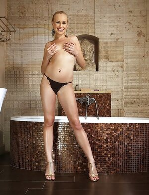 Fantastic blonde with ponytail impresses boys with awesome assets by bathtub