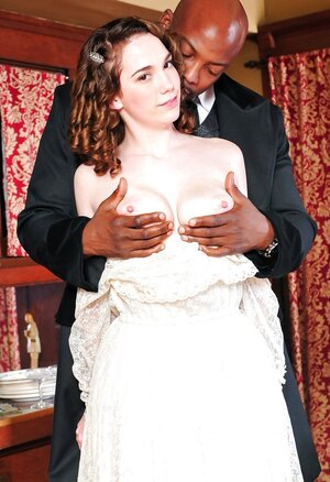 Pale-skinned gal in old-fashioned white dress kisses black lad in a suit