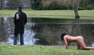 Master walks with dominated naked brunette on a leash and additionally ties her up to the tree