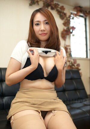 Breathtaking Japanese babe with red hair exposes on leather couch her assets