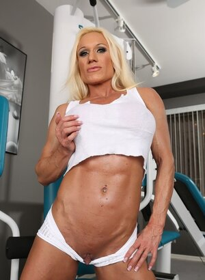 Lady bodybuilder in white top and transparent shorts prefers to train nude